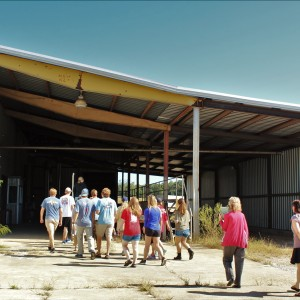 Students head inside an old cotton gin, followed by Dr. McKee and Rebecca Cleary